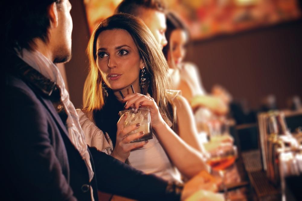 young man and young woman talking at bar